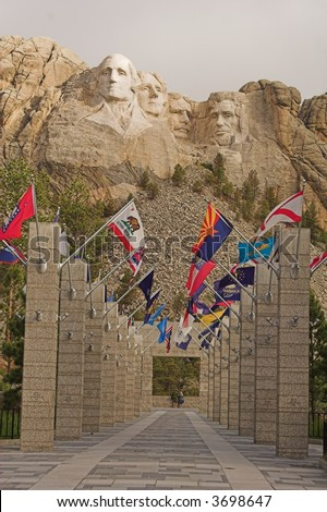Mount Rushmore and the aisle of the flags of the 50 United States.  Two observers can be seen at the end of the corridor.