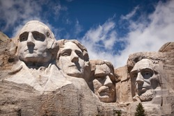 Mount Rushmore National Memorial, four ex Presidents faces sculptured into granite with blue sky and cloud background, Mount Rushmore, South Dakota, USA