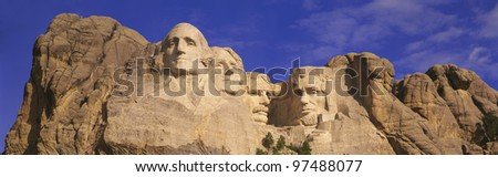 Mount Rushmore National Monument against a blue sky. Faces of George Washington, Thomas Jefferson, Theodore Roosevelt, and Abraham Lincoln.
