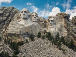 Mount Rushmore with a blue sky and clouds