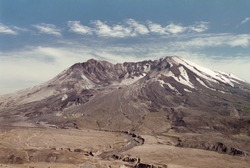 Mount Saint Helens in 1997- Mt. St. Helens lit by setting sun in the evening. The volcano, crater, dome and lava flow (post May 18, 1980 eruption) can be seen. Grainy photo shot in July 1997 on film.