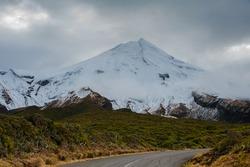 Mount Taranaki (Mount Egmont), Egmont National Park, New Zealand. Snow covered peak, dark stormy sky at dusk.