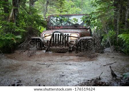 MOUNT UNIACKE, NOVA SCOTIA - JULY 4, 2009:  A Jeep drives through a deep mud bog but ends up getting stuck.