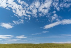 Mountain and grasslands and roads under blue sky and white clouds in Xinjiang, China in summer