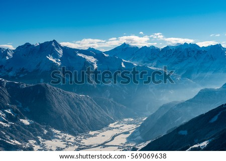 Mountain and valley winter scenic view with snow and blue sky with light fog and the river Ziller in ski area of Austria, Tirol in Europe