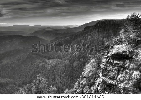 Mountain arrange in black and white color. Forest vally below sharp sandstone rocks. Black and white photo