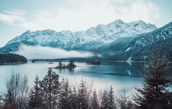 Mountain at sunrise by the lake with clouds in a winter landscape