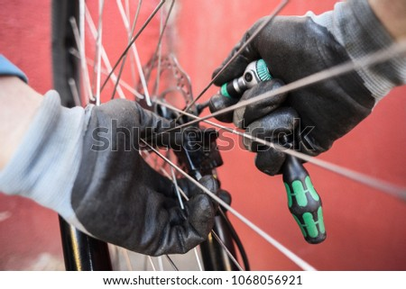 Mountain bicycle repairing. Mechanic hands at work fixing rear wheel disk brakes #1068056921