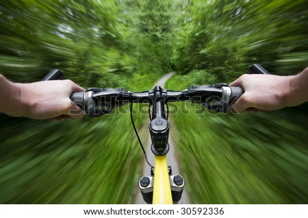 Mountain bike descending fast trough forest