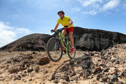 Mountain bike MTB biking man racing in mountain desert trail rocks path jumping in the air riding bicycle in mountains. Professional bicycle rider training outdoors. Sports and fitness.