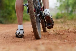 Mountain bike rear wheel and riders foot. Back shot of mountain bike on brown dirt road. Close up view of a Mountain bike tire.