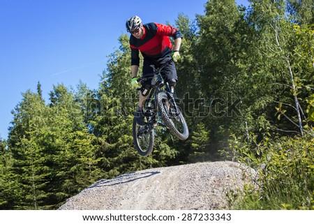 Mountain bike rider jumps over a dirt track kicker