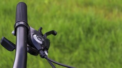 Mountain bike steering wheel on green grass background. Details of sporting events. Close up black mountain bike knob and derailleur knob, left shifter