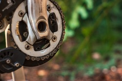 Mountain bike used and dirty front crank drive and link chain close up shot outside.