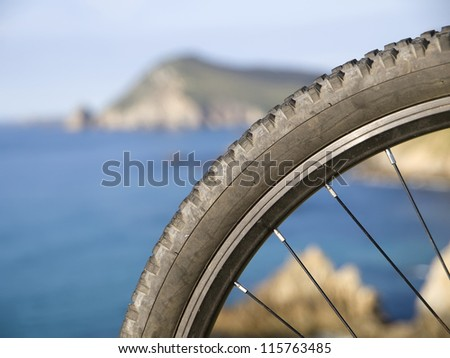 ... mountain bike wheel and a seascape in the background - stock photo
