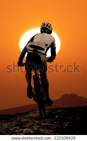 Mountain biker agonizes uphill during sunset