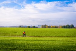 Mountain biker cyclist in countryside Zottegem, Flanders, Belgium. Mountainbike in motion riding through sunny grass field with trees in horizon. Fields in Autumn or fall in Flemish Ardennes, Belgium.