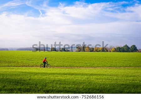 Mountain biker cyclist in countryside Zottegem, Flanders, Belgium. Mountainbike in motion riding through sunny grass field with trees in horizon. Fields in Autumn or fall in Flemish Ardennes, Belgium. #752686156