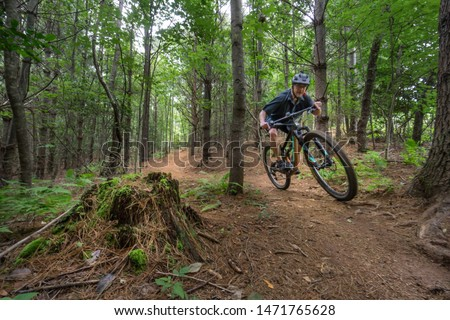 Mountain biker flies through the lush forest greenery on the trail in Lake James park, North Carolina. These trails are fast flowing and enjoyable, providing sport, fitness, motivation and inspiration