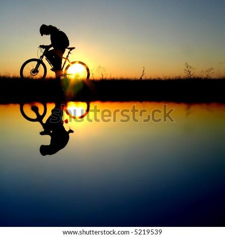 mountain biker girl silhouette in sunrise - stock photo