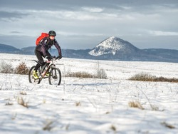 Mountain biker in snowy landscape. Sportsman properly equiped for winter cycling is ridding in heavy terrain.  Sunny winter weather and snow.