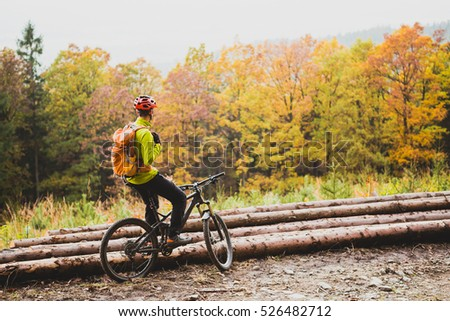 Mountain biker looking at inspiring mountain landscape, standing with bicycle. Man cycling MTB on dirty road in woods. Sport and active recreation, fitness motivation and inspiration.