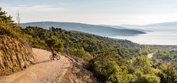 Mountain biker looking at view, riding on bike in autumn inspirational mountains landscape. Man cycling biking on dirt road. Sport fitness motivation and inspiration MTB rider training, Croatia.