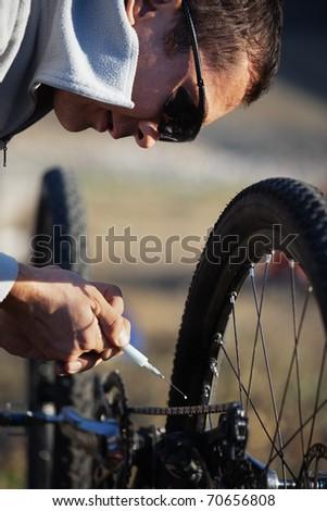 Mountain biker lubricate bicycle chain