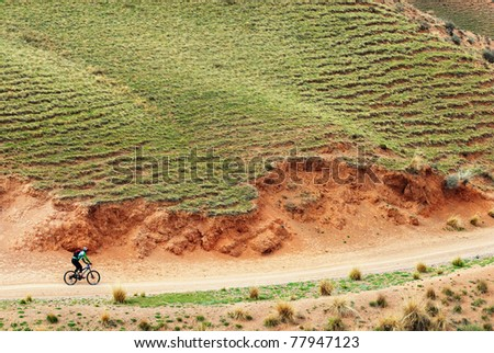 Mountain biker on rural road in desert mountains, Kazakstan