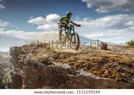 Mountain biker on trail. Male cyclist rides the rock