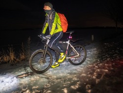 Mountain biker ride alone in snowy winter night. Sportsman properly equiped for winter cycling is ridding in terrain.  Cold winter weather and snow.