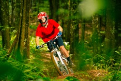 Mountain Biker Riding Down Beautiful Lush Forest Trail in the Mountains