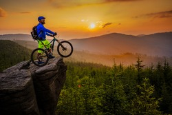 Mountain biker riding on bike in autumn mountains forest landscape. Man cycling MTB flow trail track. Outdoor sport activity.