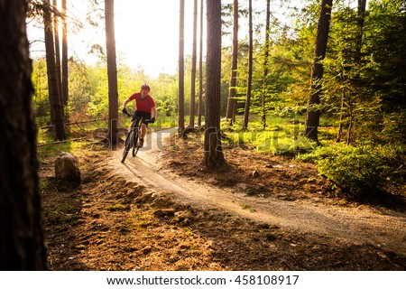 Mountain biker riding on bike in spring inspirational mountains landscape. Man cycling MTB on enduro trail track. Sport fitness motivation and inspiration outdoors in sunset woods. #458108917