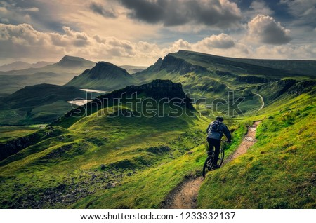 Mountain biker riding through rough mountain landscape of Quiraing, Isle of Skye, Scotland, UK