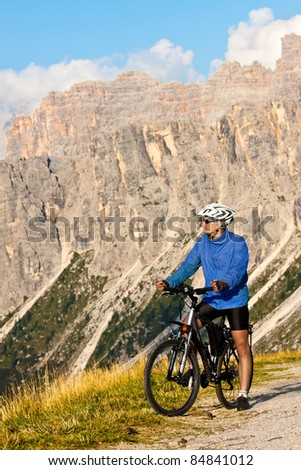 Mountain biker with rocky mountains. Alps