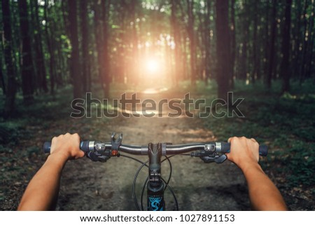Mountain biking down hill descending fast on bicycle. View from bikers eyes. #1027891153