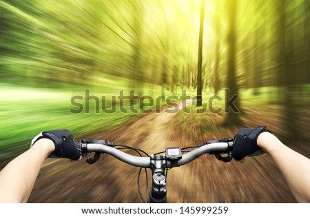 Mountain biking down hill descending fast on bicycle. View from bikers eyes.  #145999259