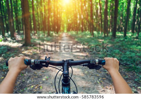 Mountain biking down hill descending fast on bicycle. View from bikers eyes. #585783596