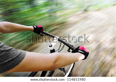 Stock Photo Mountain biking down hill descending fast. View from bikers eyes. Motion blurred