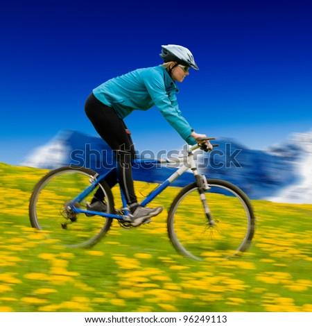 Mountain biking down  - woman downhill on bike in dandelion, snowy mountain peaks in the background - stock photo