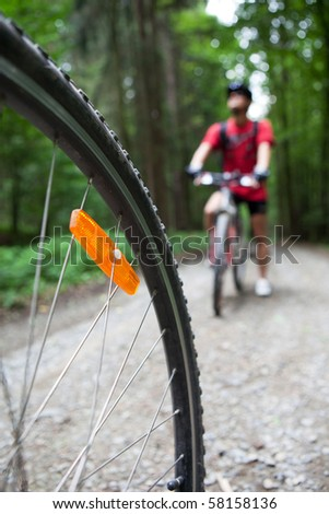 Mountain biking in a forest - bikers on a forest biking trail (shallow DOF, focus on the bike wheel in the foreground)