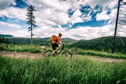 Mountain biking man riding on bike in summer inspirational landscape. Bikepacking, cycling on enduro trail. Sport fitness motivation and inspiration. MTB Rider mountain biker in summer woods.