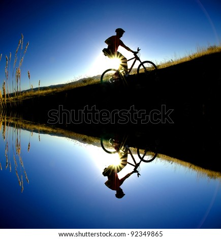 Mountain biking up a trail in the mountains silhouetted reflection in water