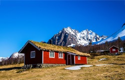 Mountain cabin at snowy peak. Red wooden cabin in mountains. Mountain cabin view. Cabins in mountains