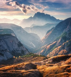 Mountain canyon lighted by bright sunbeams at sunset in autumn in Dolomites, Italy. Landscape with mountain ridges, rocks, colorful trees and orange grass, alpine meadows, gold sunlight in fall. Alps