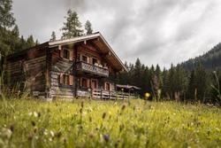 Mountain chalet and cloudy sky in Austria: Idyllic landscape in the Alps