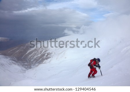 Mountain climber in bad weather during winter