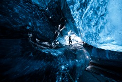 Mountain climber standing inside an icecave in a glacier in Iceland