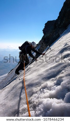mountain climber traverses a blank ice field on a high alpine peak with a great view behind #1078466234